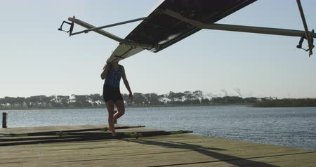 scull : Front view of a young adult Caucasian female rower carrying a racing shell on her shoulder walking on a jetty after training on a river