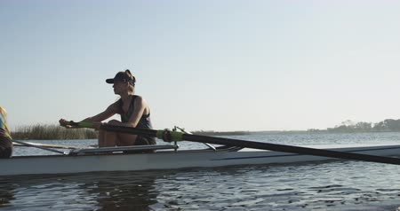 evezős : Side view close up of two young adult Caucasian women rowing in a racing shell on a river during training