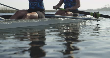 scull : Side view close up of two young adult Caucasian women rowing in a racing shell on a river during training