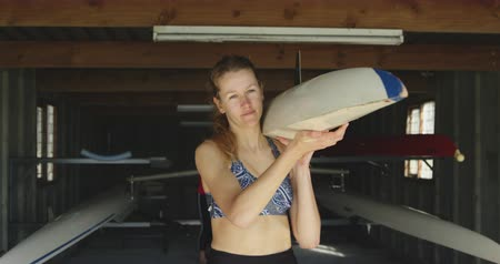 evezős : Front view of a young adult Caucasian female rower standing in a boatshed carrying one end of a racing shell before training on a river, her colleague carrying the other end of the boat in the background