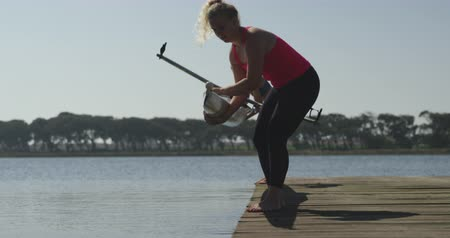 scull : Side view of a young adult Caucasian female rower standing on a jetty and lowering a racing shell into a river before training, with her colleague holding the other end of the boat in the background