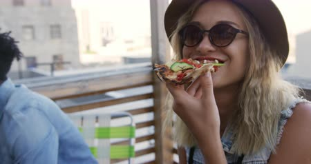 socialising : Front view of a happy young Caucasian woman enjoying herself at party on a rooftop, eating a sandwich with a happy young African American male friend in the background