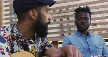 socialising : Side view close up of a happy young mixed race man holding a guitar and talking to a young African American male friend, enjoying themselves at a party on a rooftop Stock Footage