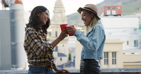 estilo livre : Side view of a happy young Caucasian and mixed race female friends enjoying themselves at party on a rooftop, smiling, talking and drinking, with buildings in the background