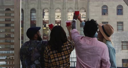 vrijen : Rear view of a group of happy young multi-ethnic male and female friends enjoying themselves at a party on a rooftop, raising cups in a toast, with a building in the background