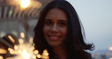on camera : Portrait of a happy young mixed race woman enjoying herself at a party on a rooftop smiling and holding sparklers