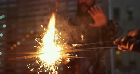 estilo livre : Front view of a happy young mixed race man enjoying himself at a party on a rooftop, holding sparklers with his friends