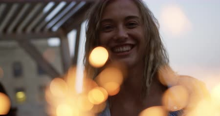 socialising : Front view of a happy young Caucasian woman enjoying herself at a party on a rooftop smiling and holding a sparkler