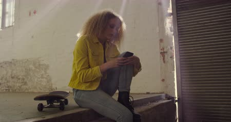 tárcsáz : Side view of a hip young Caucasian woman in an empty warehouse, using a smartphone sitting next to a skateboard
