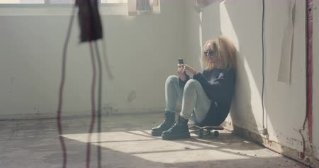 tárcsázás : Side view of a hip young Caucasian woman in an empty warehouse, using a smartphone sitting on a skateboard