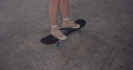 nem városi színhely : Legs of a hip young Caucasian woman in an empty warehouse, riding on a skateboard
