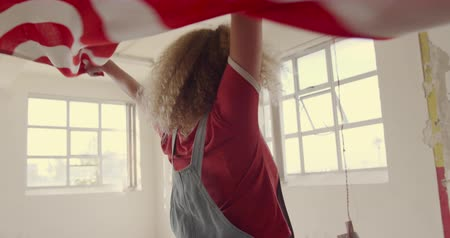 cultura juvenil : Front view of a hip young Caucasian woman in an empty warehouse, dancing with an American flag