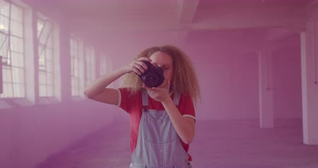 grenade : Front view of a hip young Caucasian woman in an empty warehouse, taking photos surrounded by pink smoke from a hand grenade