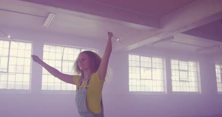 generation : Front view of a hip young Caucasian woman in an empty warehouse, dancing with sparklers surrounded by purple smoke from a hand grenade