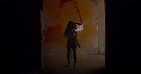 grenade : Front view of a hip young Caucasian woman in an empty warehouse, walking with a hand grenade