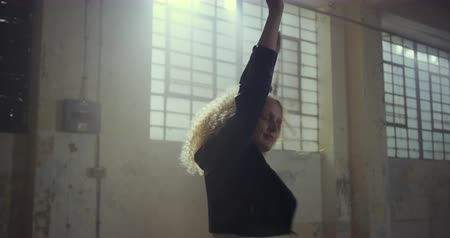 estilo livre : Front view of a hip young Caucasian woman in an empty warehouse, dancing with a glowstick