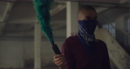 granada : Side view of a hip young mixed race man in an empty warehouse, holding a hand grenade with bandana covering his face