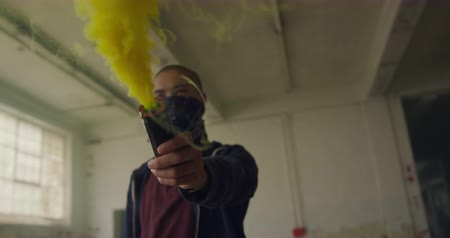 grenade : Side view of a hip young mixed race man in an empty warehouse, holding a hand grenade with bandana covering his face