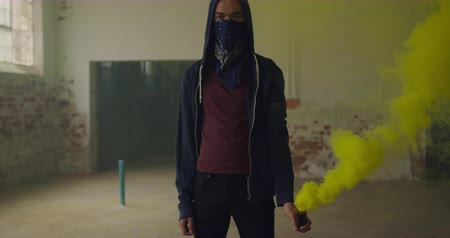 grenade : Front view of a hip young mixed race man in an empty warehouse, holding a hand grenade with bandana covering his face and a hood on