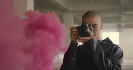 grenade : Front view of a hip young mixed race man in an empty warehouse, taking photos with pink smoke from a hand grenade behind him Stock Footage