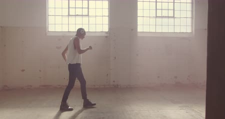 cultura juvenil : Side view of a hip young mixed race man in an empty warehouse, dancing and listening to music with headphones on