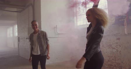 grenade : Front view of a hip young mixed race man and a hip young Caucasian woman in an empty warehouse, walking, the woman holding a hand grenade and turning around