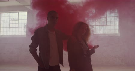 quadris : Portrait of a hip young mixed race man and a hip young Caucasian woman in an empty warehouse, the woman holding a hand grenade Stock Footage