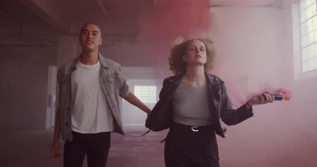 grenade : Front view of a hip young mixed race man and a hip young Caucasian woman in an empty warehouse, holding hands and running, the woman holding a hand grenade