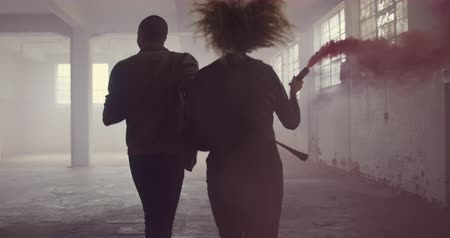 grenade : Rear view of a hip young mixed race man and a hip young Caucasian woman in an empty warehouse, holding hands and running, the woman holding a hand grenade Stock Footage
