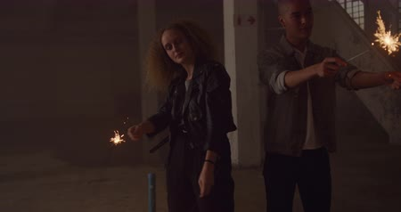 csillagszóró : Front view of a hip young mixed race man and a hip young Caucasian woman in an empty warehouse, holding sparklers and the woman dancing