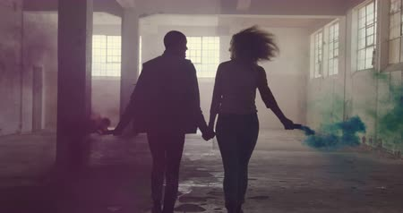 grenade : Rear view of a hip young mixed race man and a hip young Caucasian woman in an empty warehouse, running holding hands and holding hand grenades Stock Footage