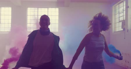grenade : Front view of a hip young mixed race man and a hip young Caucasian woman in an empty warehouse, running holding hands and holding hand greanades