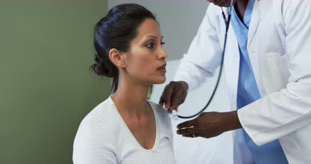 almofadas : Front view of African american male doctor examining female patient in the ward at hospital. He is using stethoscope
