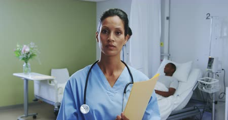 reszelő : Front view of African american female doctor looking at camera in the ward at hospital. Male doctor talking with male patient at bed