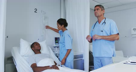 glikoz : Front view of Caucasian male doctor using invisible screen in ward at hospital. Female doctor adjusting iv drip