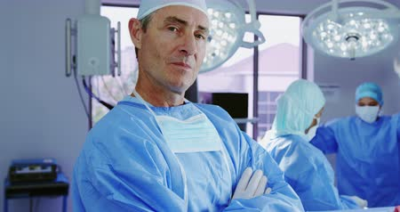 surgical light : Close-up of mature Caucasian female doctor standing with arms crossed in hospital. He is smiling and looking at camera