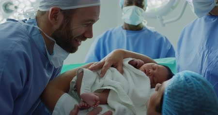 operation theater : Close-up of Caucasian couple looking at their newborn baby in hospital. They are interacting with each other