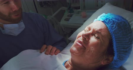 operation theater : Close-up of Caucasian man comforting pregnant woman during labor in operation theater. He is holding her hand Stock Footage