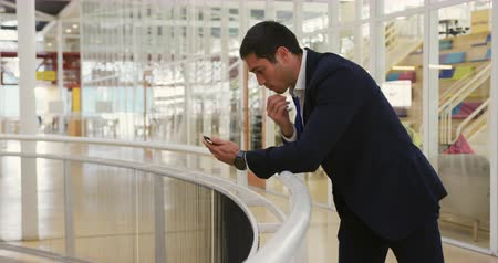 lobi : Side view of a young Caucasian businessman leaning on a handrail using a smartphone in the foyer at a business conference Stok Video