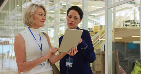 объяснять : Front view close up of two Caucasian businesswomen talking, looking at a tablet computer and shaking hands in the foyer at a business conference