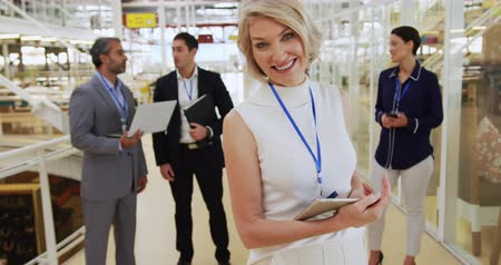 socialising : Front view close up of a middle aged Caucasian businesswoman holding a tablet turning around looking to camera and smiling, while a group of diverse business people talk in the background in the foyer at a business conference