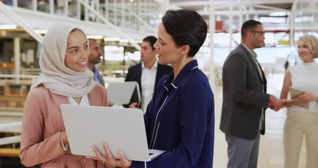 delegate : Front view close up of a young Asian businesswomen wearing a hijab and a yong Caucasian businesswoman using a laptop computer talking in the lobby of a business conference, with a diverse group of business people talking in the background