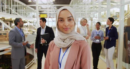 delegate : Portrait close up of a young Asian businesswoman wearing hijab and holding a smartphone, turning around looking to camera and smiling, while a group of diverse business people talk in the background in the foyer at a business conference