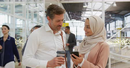 socialising : Front view close up of a middle aged Caucasian businessman drinking a coffee talking with a young Asian businesswoman wearing a hijab showing him her smartphone in the foyer of a business conference, with business people walking in the background