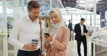 delegate : Front view close up of a middle aged Caucasian businessman holding a coffee talking to a young Asian businesswoman wearing a hijab using a smartphone at the foyer of a business conference, with business people walking in the background
