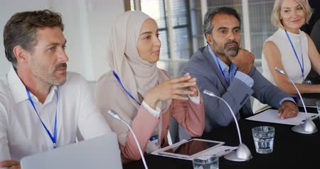 delegate : Side view close up of four business delegates, a young Caucasian man, a young Asian woman wearing a hijab, a middle aged mixed race man and a middle aged Caucasian woman, sitting in a row at a table with microphones in front of them listening to questions Stock Footage