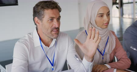 delegeren : Elevated side view of two business delegates, a young Caucasian man and a young Asian woman wearing a hijab, sitting at a table with microphones in front of them at a business conference. The young man is talking and gesturing while the woman listens