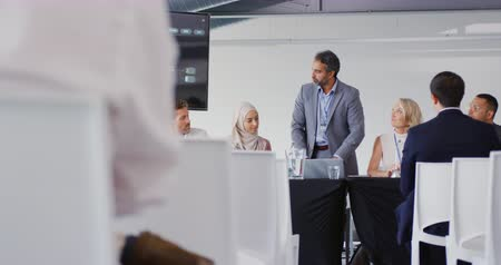 escuta : Front view of a middle aged mixed race businessman standing to address an audience, flanked by seated colleagues and delegates at a business conference. The back of the audience visible in the foreground Stock Footage