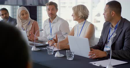 delegeren : Front view of a young Caucasian businessman sitting at the centre of a row of five diverse business delegates at a table with microphones in front of them at a business conference. The young man is speaking and looking to the audience while his colleagues Stockvideo