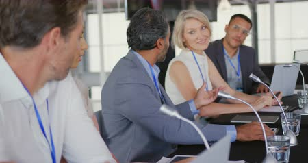 advisor : Side view of a middle aged mixed race businessman sitting at the centre of a row of five diverse business delegates at a table with microphones in front of them at a business conference. The middle aged man is speaking and looking to his colleagues on the Stock Footage